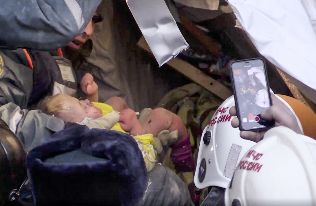 This photo provided by the Russian Emergency Situations Ministry taken from tv footage shows Emergency Situations employees save a 10 month old baby a...