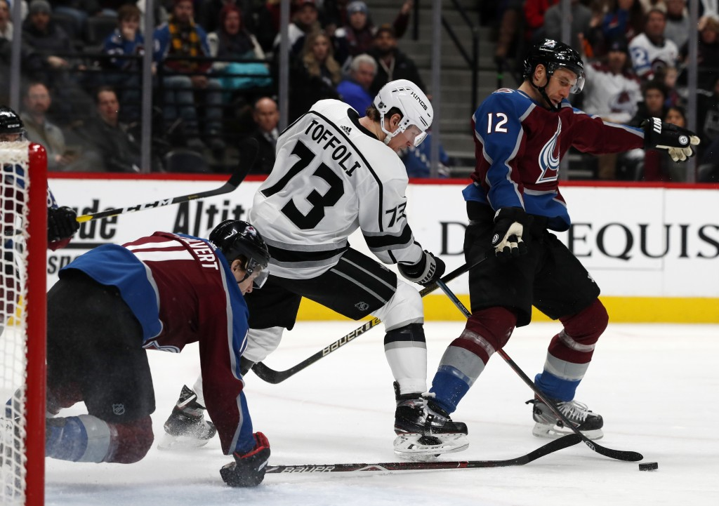 Los Angeles Kings right wing Tyler Toffoli, center, battles for control of the puck with Colorado Avalanche left wing Matt Calvert, left, and defensem...