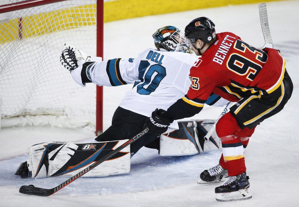 San Jose Sharks goalie Aaron Dell, left, stops a breakaway by Calgary Flames' Sam Bennett during the third period of an NHL hockey game Monday, Dec. 3