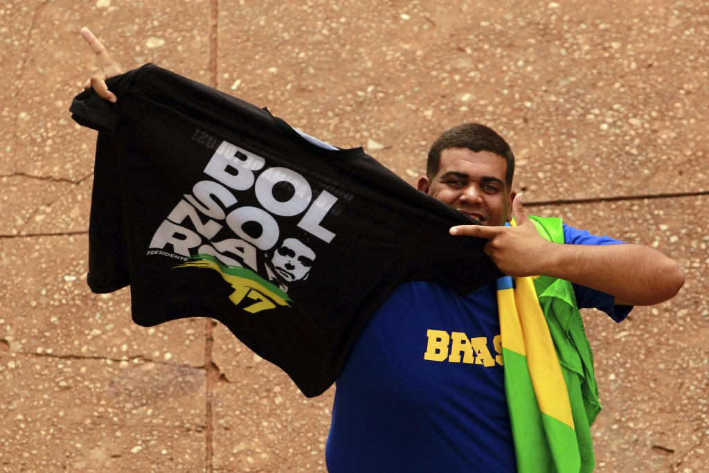 A supporter shows a T-shirt with the name of the Brazil's President-elect Jair Bolsonaro, prior to Bolsonaro's Tuesday's inauguration ceremony, in Bra...