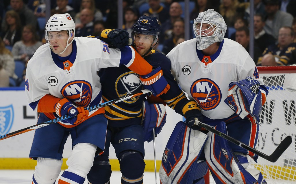 Buffalo Sabres forward Jason Pominville (29) skates between New York Islanders defenseman Scott Mayfield (24) and goalie Robin Lehner (40) during the ...