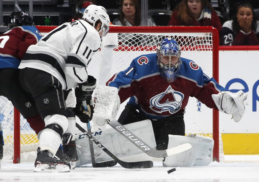 Los Angeles Kings center Anze Kopitar, left, shoots the puck at Colorado Avalanche goaltender Semyon Varlamov during the first period of an NHL hockey...