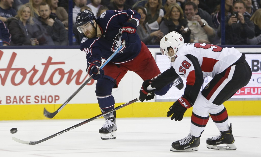 Columbus Blue Jackets' David Savard, left, shoots on goal as Ottawa Senators' Maxime Lajoie defends during the second period of an NHL hockey game Mon...