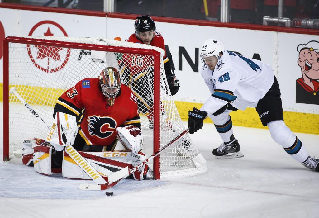 San Jose Sharks' Tomas Hertl, right, of the Czech Republic, tries to get the puck past Calgary Flames goalie David Rittich, left, of the Czech Republi
