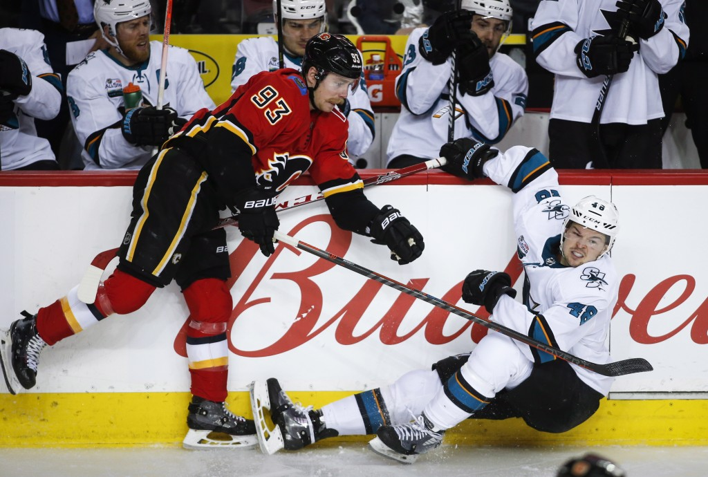 San Jose Sharks' Tomas Hertl, right, of the Czech Republic, is checked by Calgary Flames' Sam Bennett during the third period of an NHL hockey game Mo