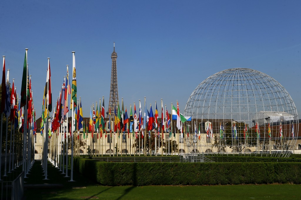FILE - In this Tuesday Oct. 31, 2017 file picture, the Eiffel Tower, country flags and the Dome are seen from the garden of the United Nations Educati...