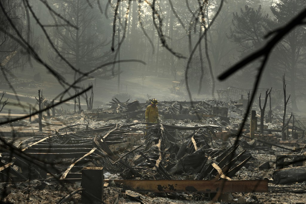 FILE - In this Friday, Nov. 16, 2018 file photo, a firefighter searches for human remains in a trailer park destroyed in the Camp Fire in Paradise, Ca