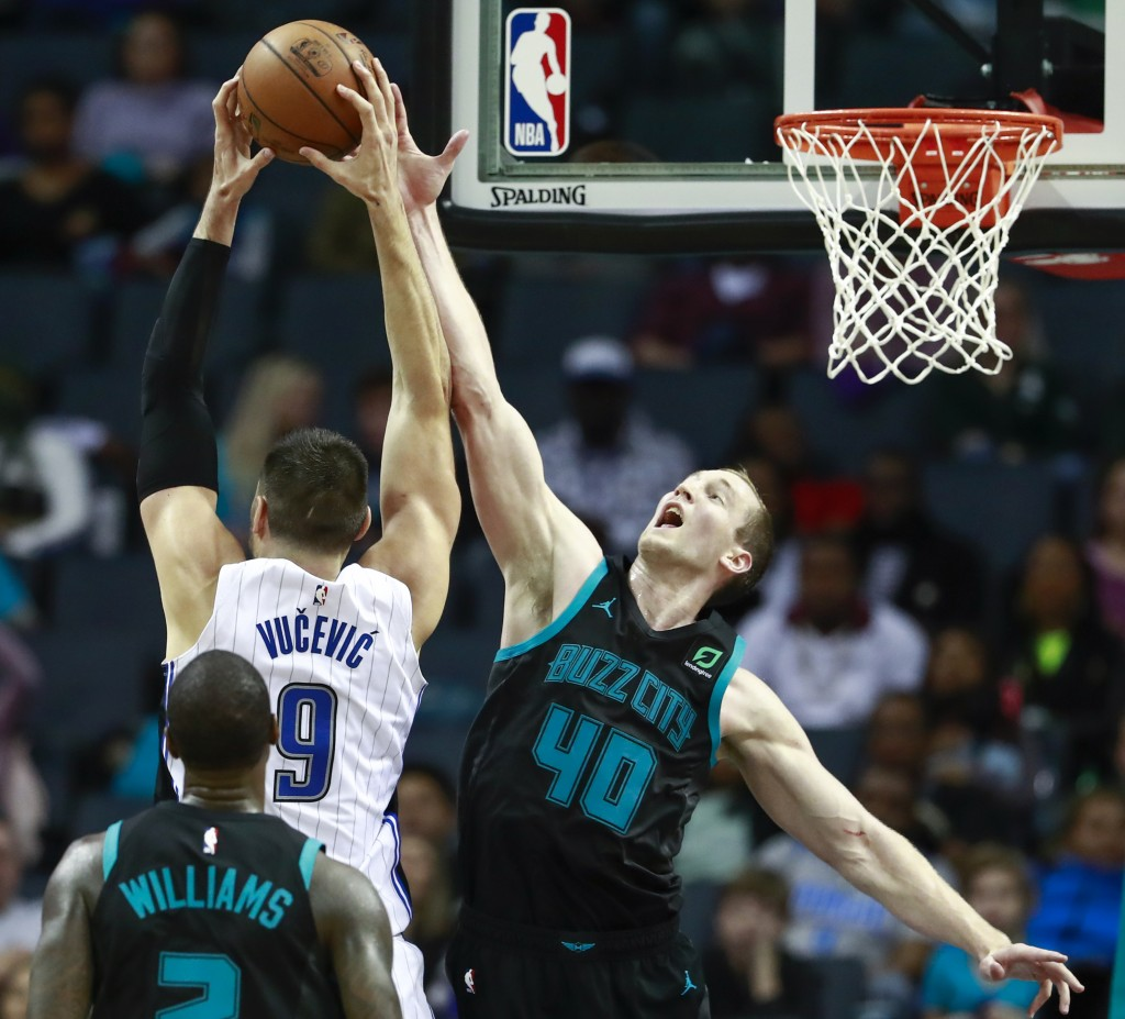 Charlotte Hornets center Cody Zeller, right, tries...