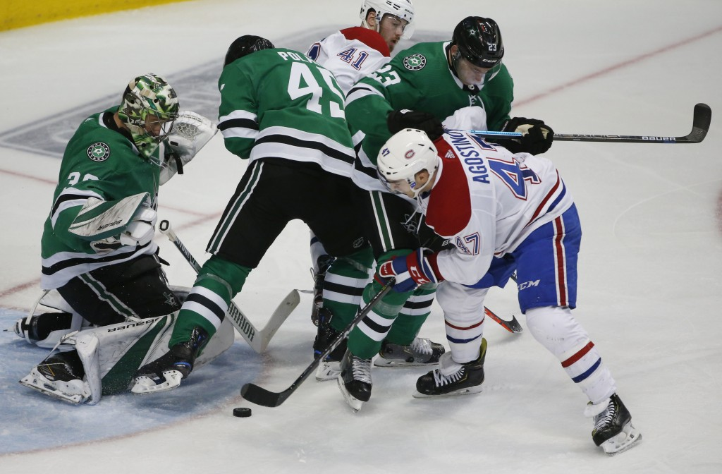 Dallas Stars goaltender Ben Bishop (30) defends as Montreal Canadiens left wing Kenny Agostino (47) tries to get the puck past Stars defenders Roman P...