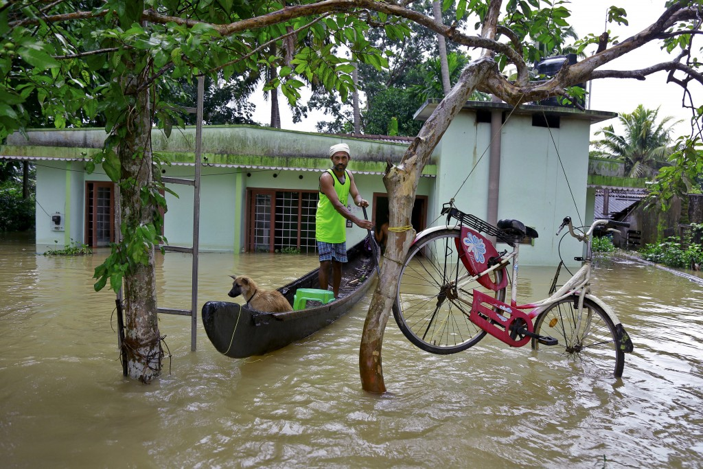 FILE - In this Monday, Aug. 20, 2018 file photo, a bicycle is hung from a tree branch to avoid being washed away in flood waters as a man rows past wi