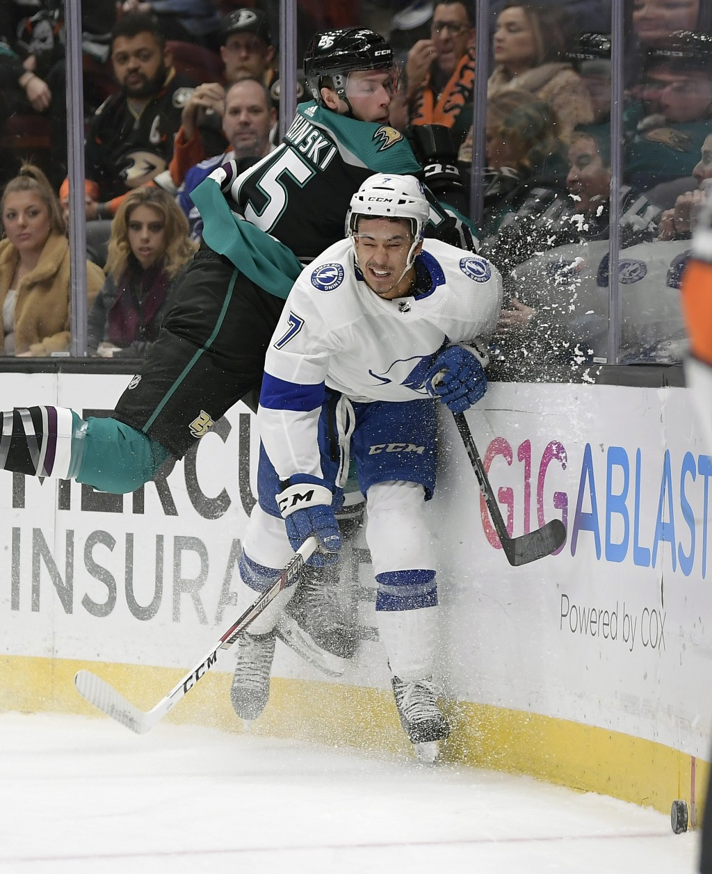 Anaheim Ducks defenseman Andy Welinski, left, and Tampa Bay Lightning right wing Mathieu Joseph battle for the puck during the first period of an NHL