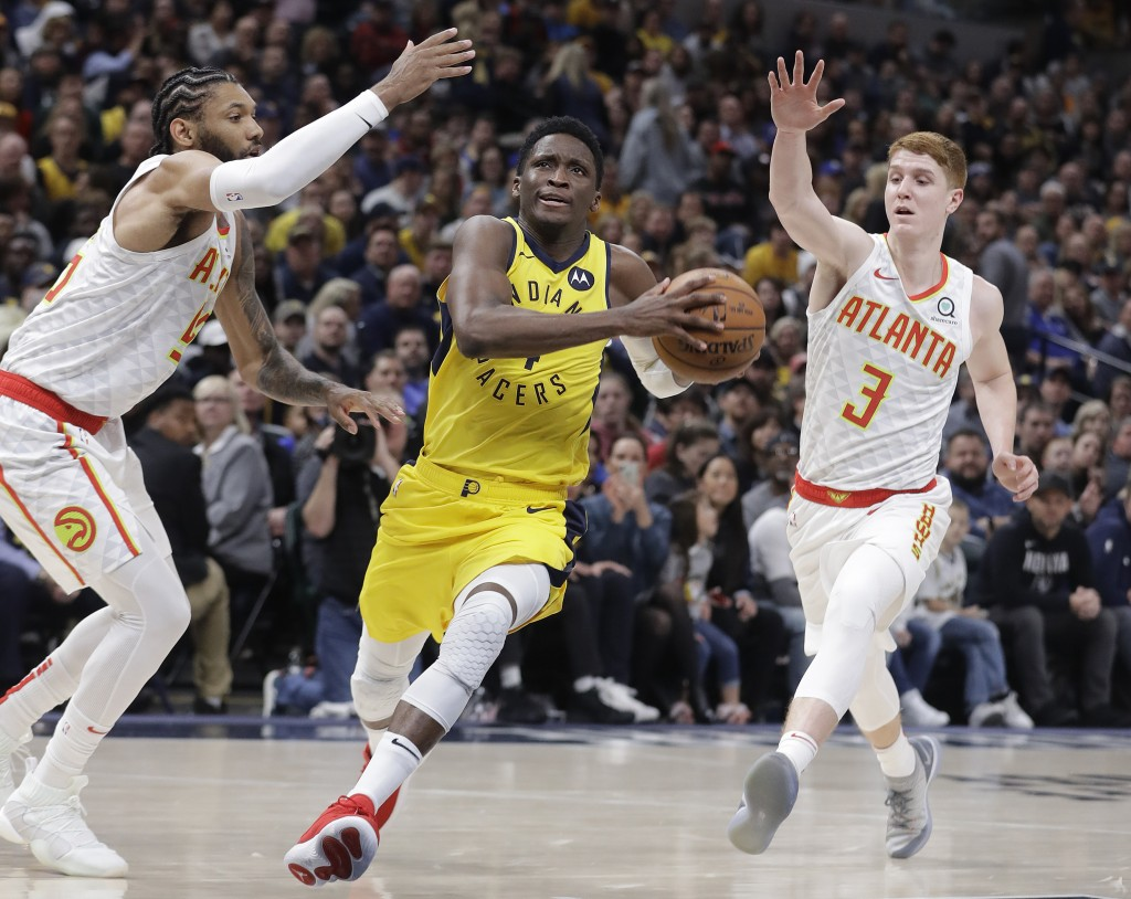 Indiana Pacers' Victor Oladipo (4) goes to the basket against Atlanta Hawks' DeAndre' Bembry (95) and Kevin Huerter (3) during the second half of an N...