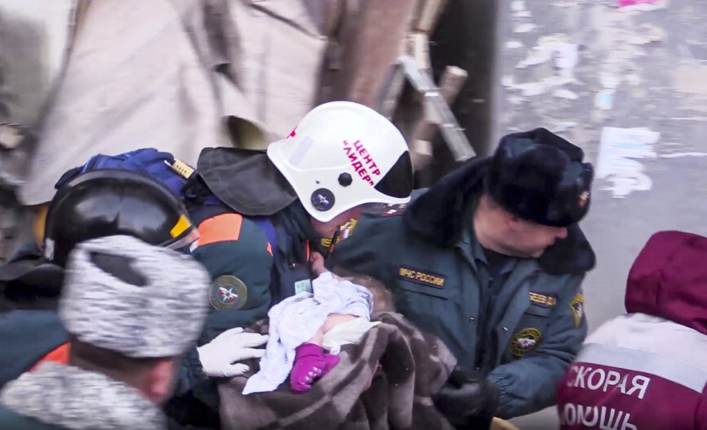 This photo provided by the Russian Emergency Situations Ministry taken from tv footage shows Emergency Situations employees carry a saved 10-month old