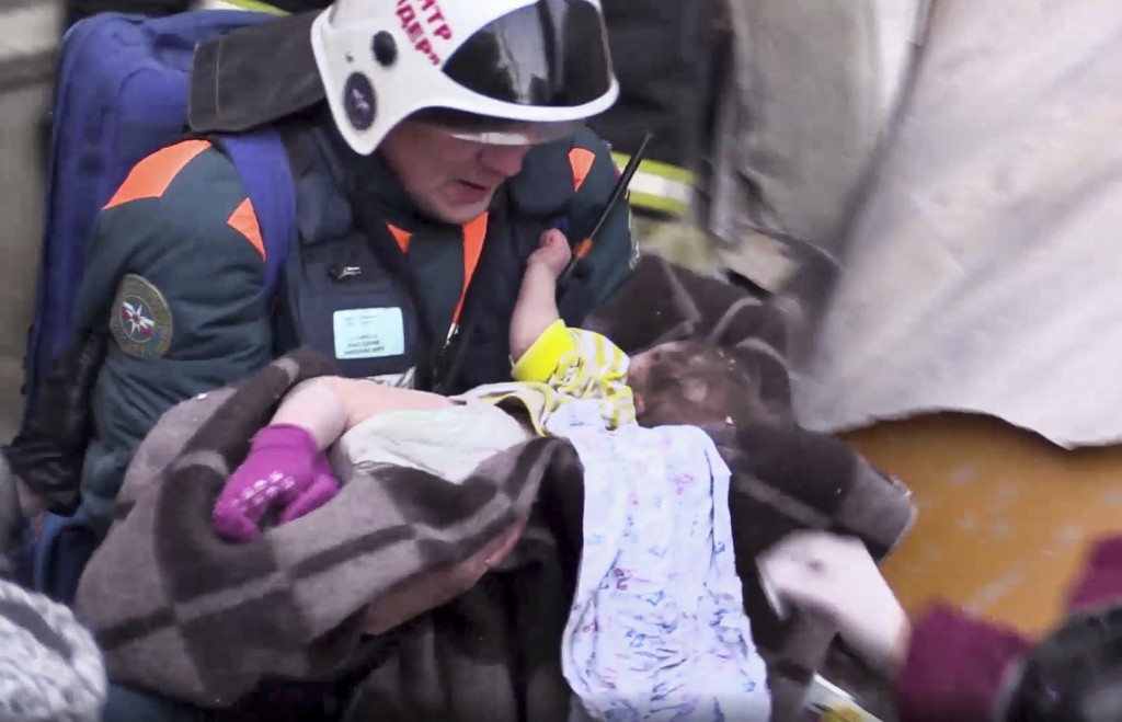 This photo provided by the Russian Emergency Situations Ministry taken from tv footage shows a Emergency Situations employee carries a saved 10 month ...
