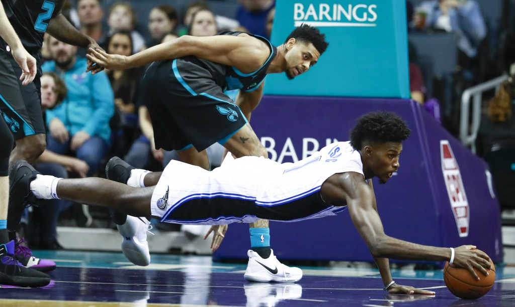 Orlando Magic forward Jonathan Isaac, right, dives...
