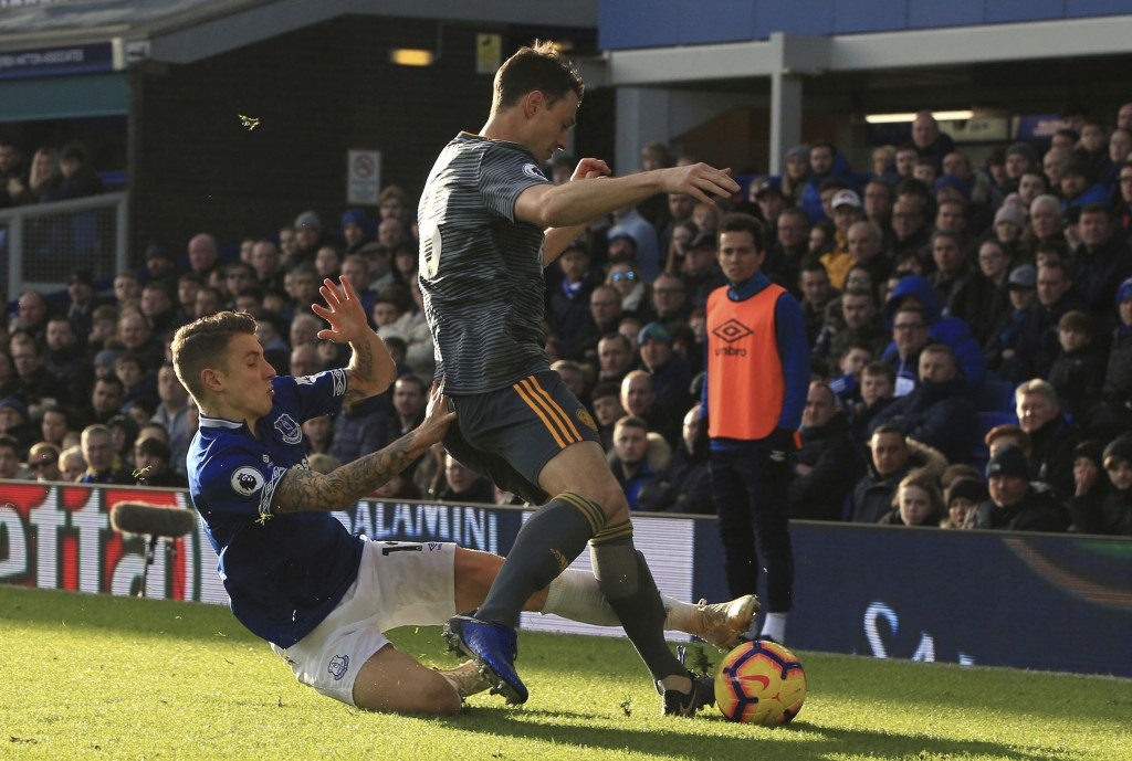 Everton's Lucas Digne, left, tries to reach the ball, around the legs of Leicester City's Jonny Evans during their English Premier League soccer match