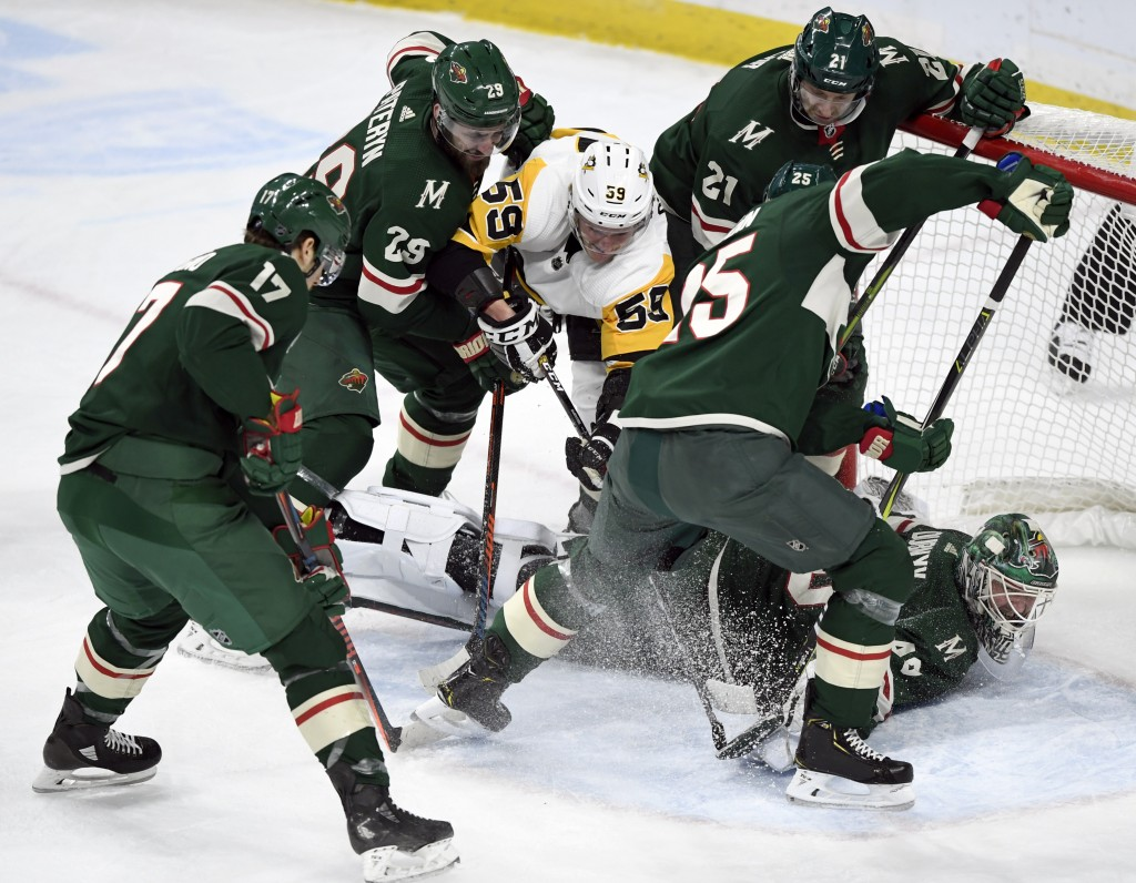 Minnesota Wild goaltender Devan Dubnyk (40) blocks a shot by Pittsburgh Penguins' Jake Guentzel (59) as Wild's Marcus Foligno (17), Greg Pateryn (29),...