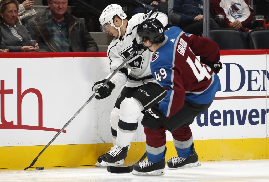 Los Angeles Kings right wing Dustin Brown, back, collects the puck along the boards as Colorado Avalanche defenseman Samuel Girard defends during the ...