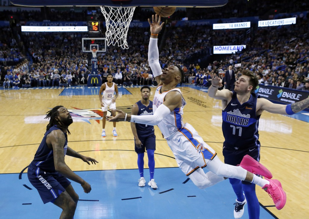 Oklahoma City Thunder guard Russell Westbrook, center, shoots between Dallas Mavericks center DeAndre Jordan, left, and Luka Doncic (77) in the first ...