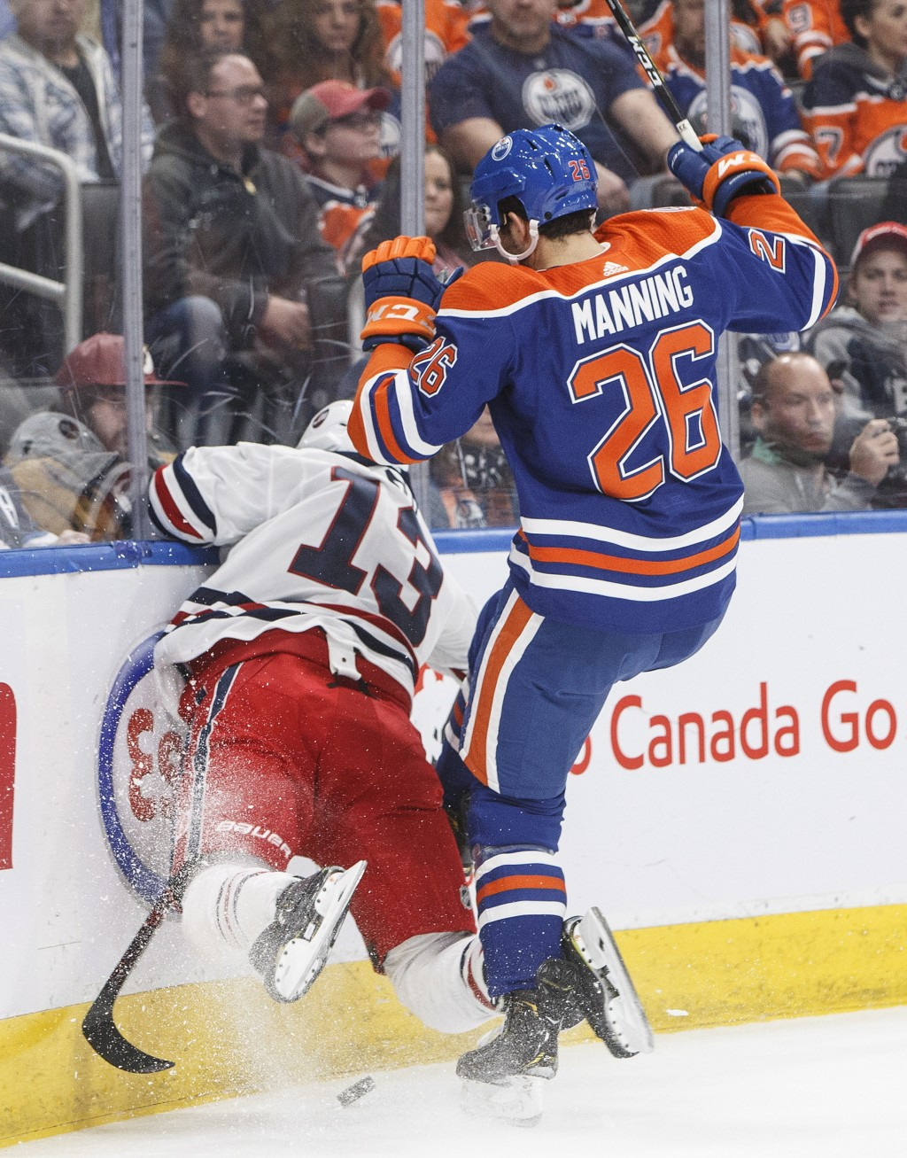 Winnipeg Jets' Brandon Tanev (13) is hit by Edmonton Oilers' Brandon Manning (26) during first-period NHL hockey game action in Edmonton, Alberta, Mon...