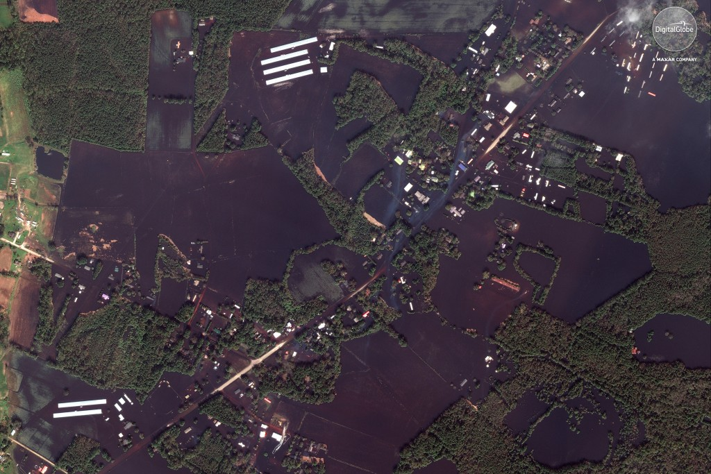 This Sept 20, 2018 satellite image provided by DigitalGlobe shows roads, farms and homes flooded from Hurricane Florence, northeast of Wallace, N.C. (