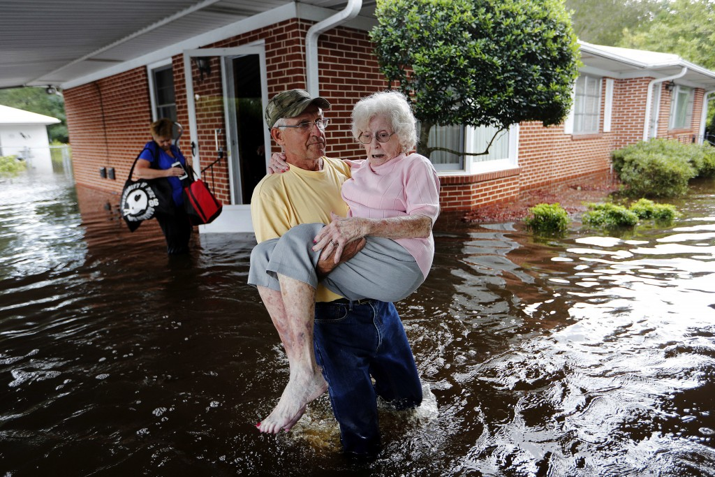 FILE - In this Sept. 17, 2018 file photo, Bob Richling carries Iris Darden, 84, out of her flooded home as her daughter-in-law, Pam Darden, gathers he