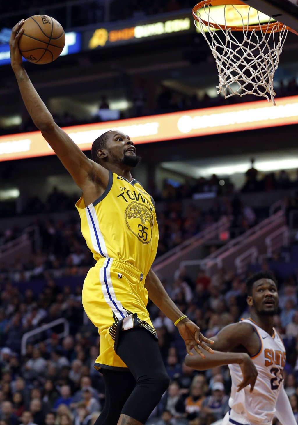Golden State Warriors forward Kevin Durant (35) dunks over Phoenix Suns center Deandre Ayton during the first half during an NBA basketball game Monda...