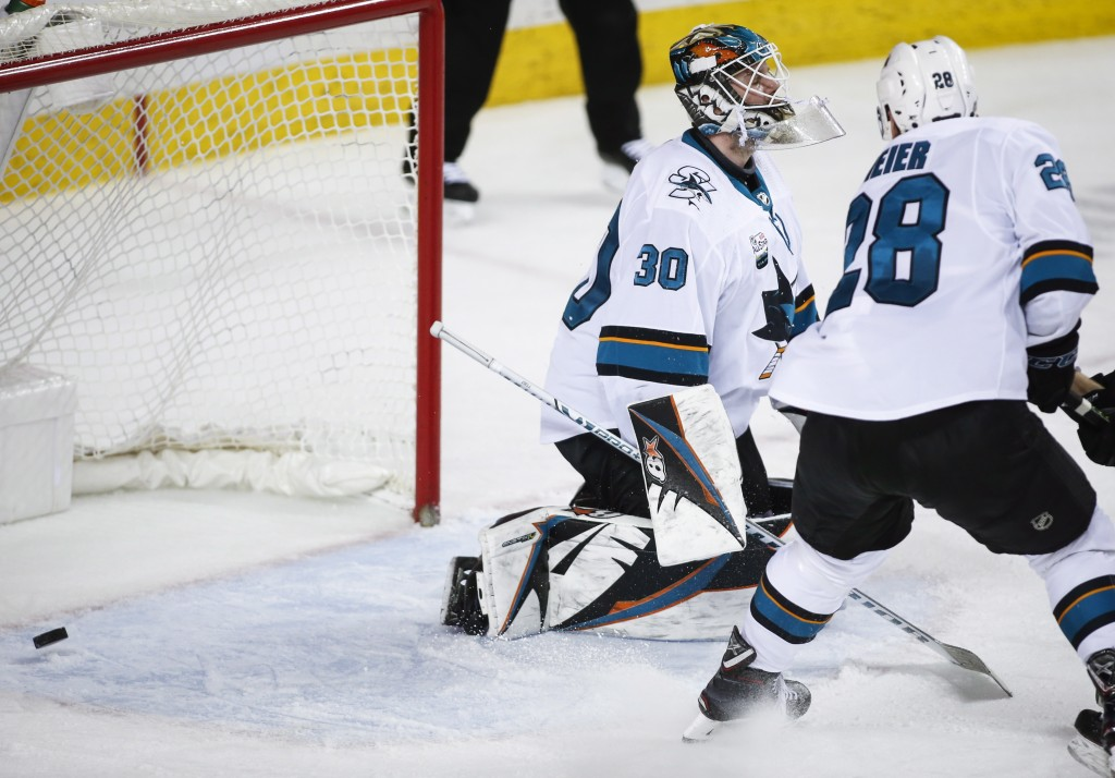 San Jose Sharks goalie Aaron Dell, left, reacts after letting in a goal by the Calgary Flames during the third period of an NHL hockey game Monday, De