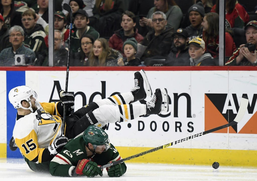 Minnesota Wild's Eric Staal (12) and Pittsburgh Penguins' Riley Sheahan (15) fall while going after the puck during the second period of an NHL hockey