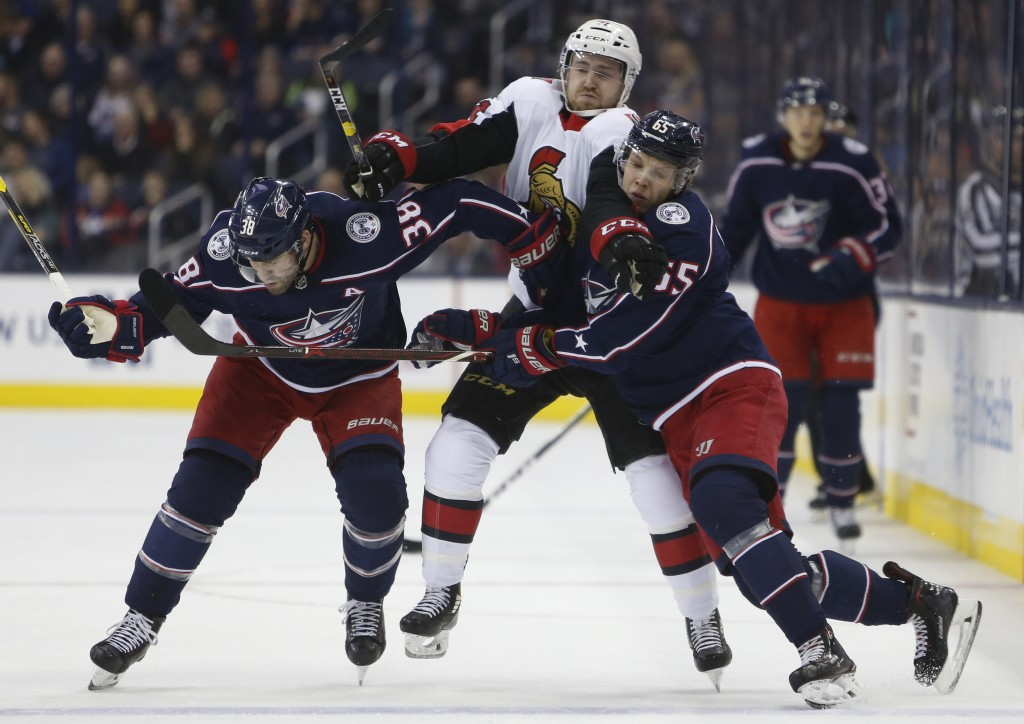 Ottawa Senators' Chris Tierney, center, tries to skate between Columbus Blue Jackets' Boone Jenner, left, and Markus Nutivaara, of Finland, during the