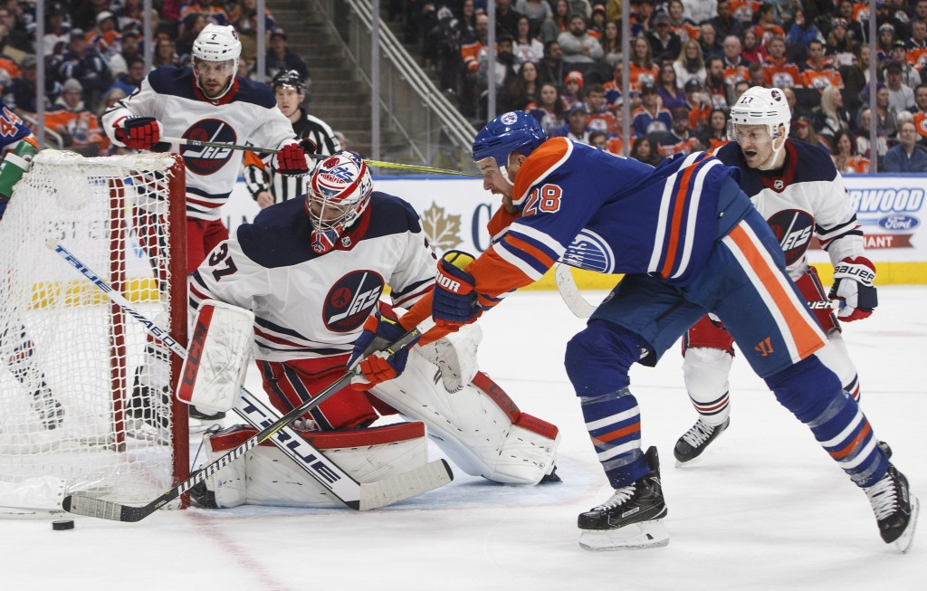 Winnipeg Jets' goalie Connor Hellebuyck (37) makes the save against Edmonton Oilers' Kyle Brodziak (28) during second-period NHL hockey game action in