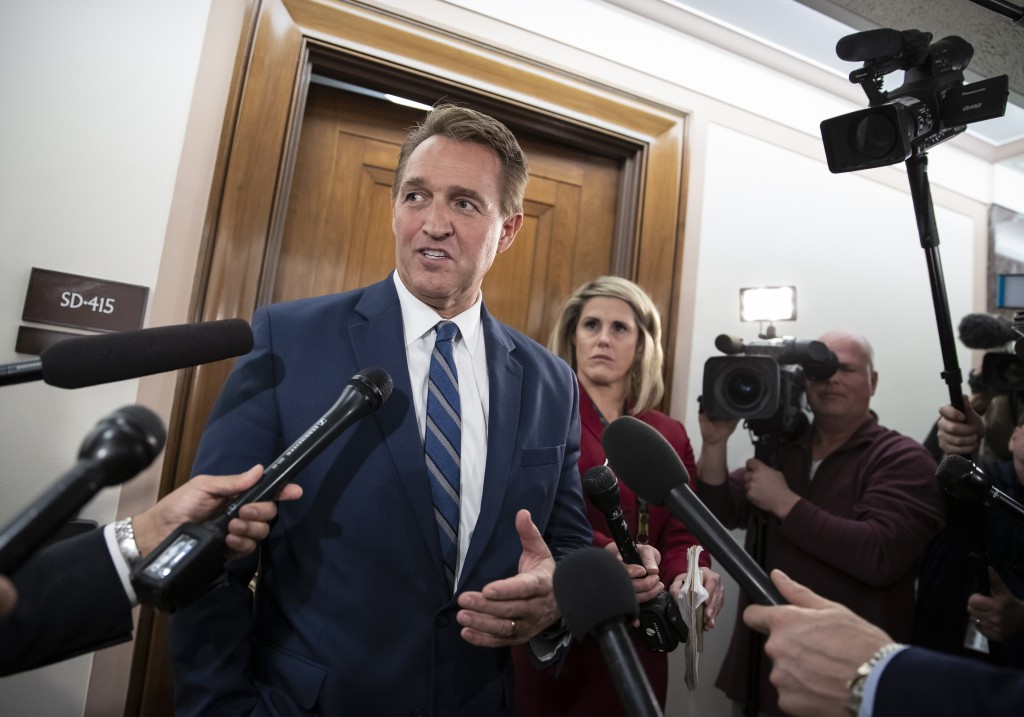 FILE- In this Dec. 6, 2018, file photo, Sen. Jeff Flake, R-Ariz., speaks with reporters on Capitol Hill in Washington.  President Donald Trump's most