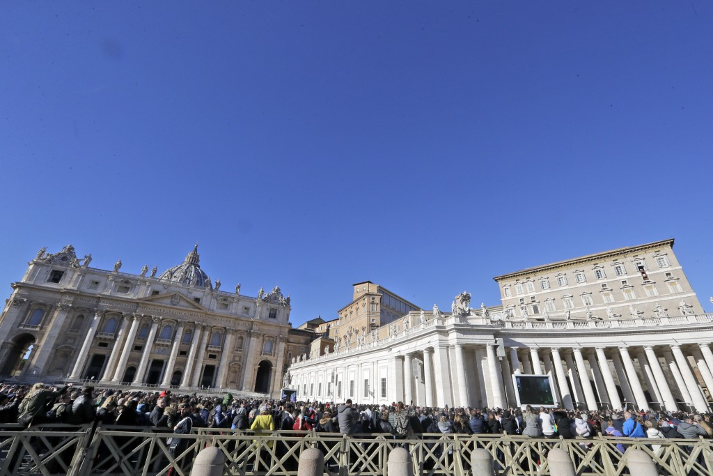 People gather in St. Peter's Square to attend a blessing by Pope Francis during the Angelus noon prayer he recited from the window of his studio overl