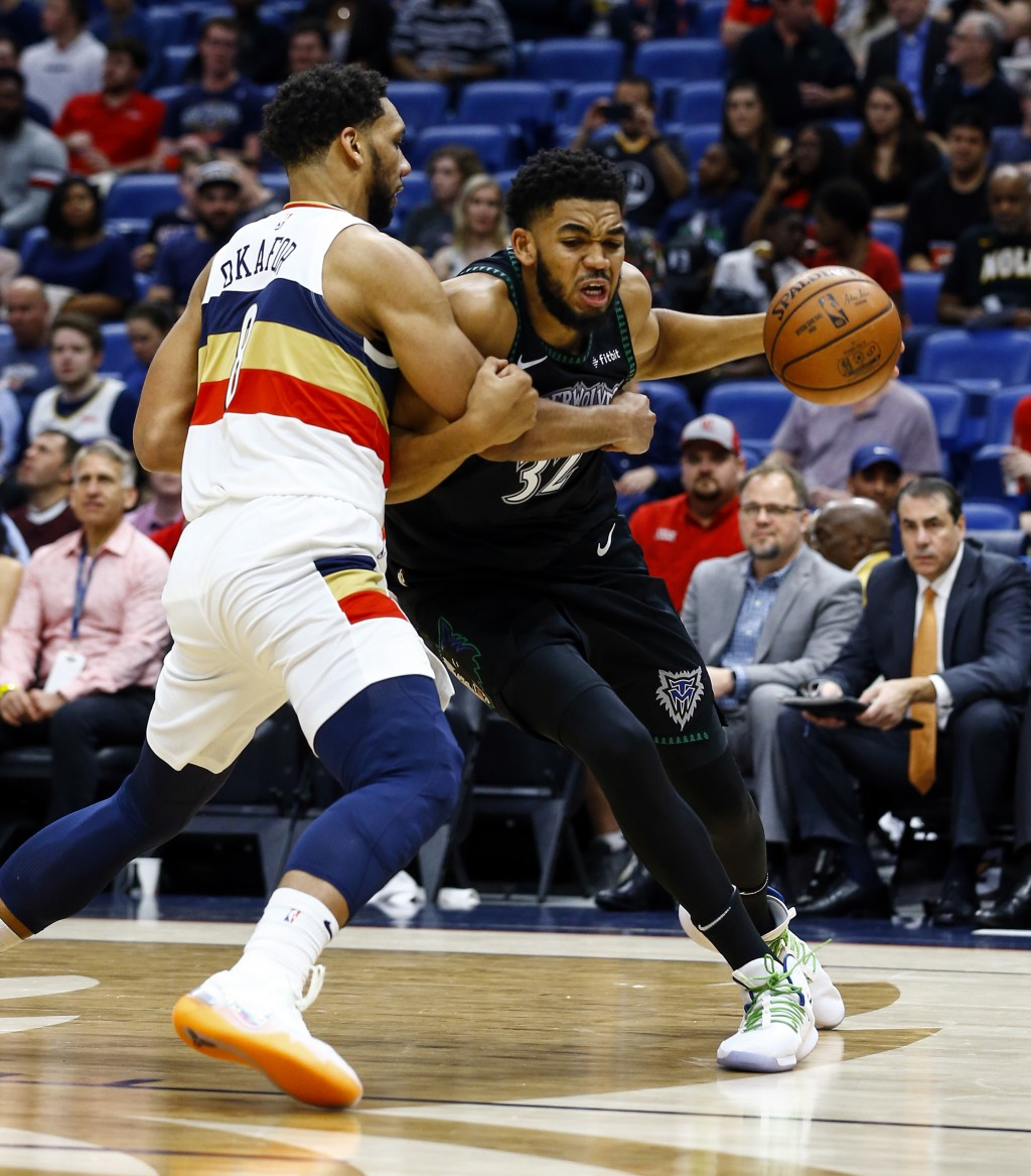 Minnesota Timberwolves center Karl-Anthony Towns (32) is fouled by New Orleans Pelicans center Jahlil Okafor (8) as he drives to the basket during the