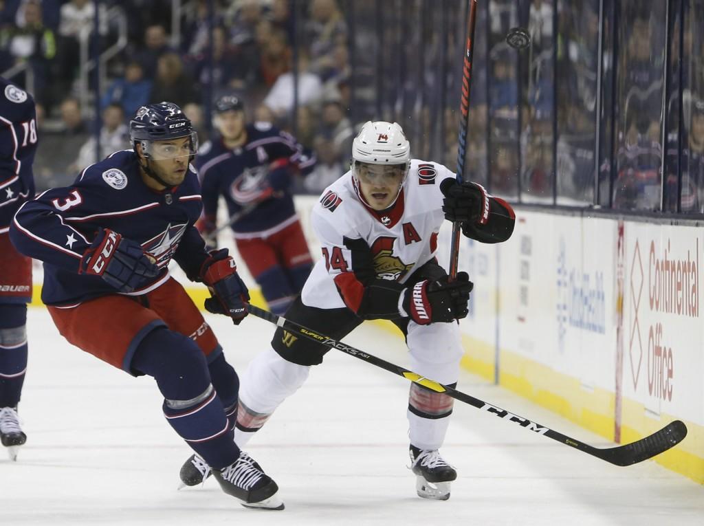 Ottawa Senators' Mark Borowiecki, right, dumps the puck past Columbus Blue Jackets' Seth Jones during the first period of an NHL hockey game Monday, D...