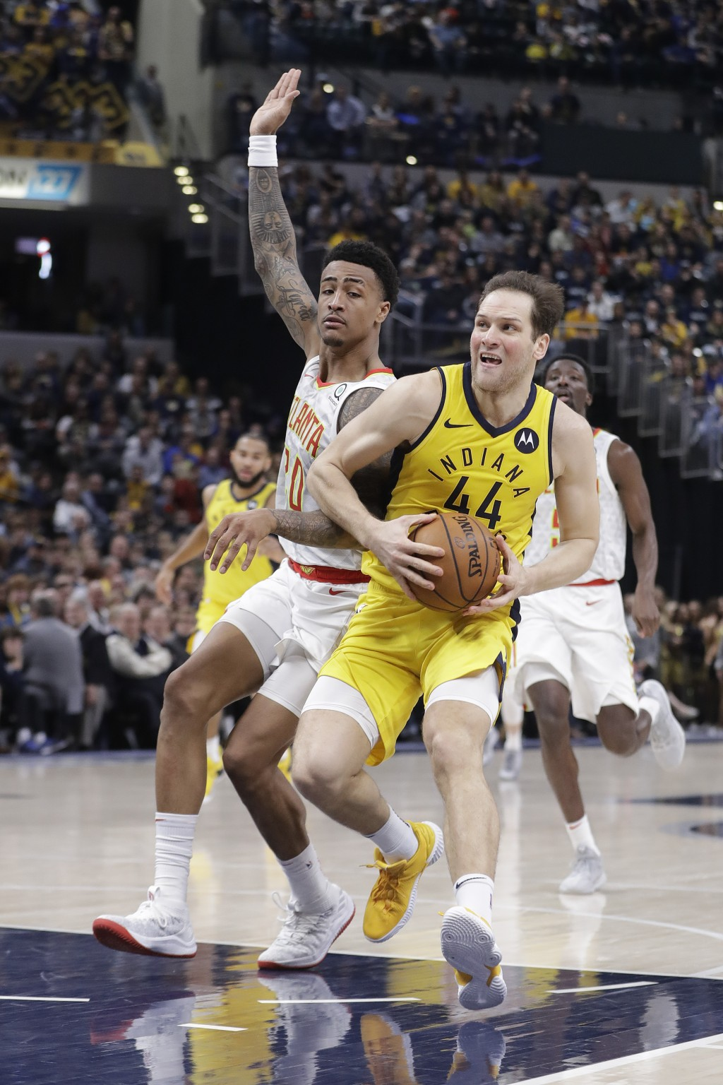 Indiana Pacers' Bojan Bogdanovic (44) goes to the basket against Atlanta Hawks' John Collins (20) during the second half of an NBA basketball game, Mo