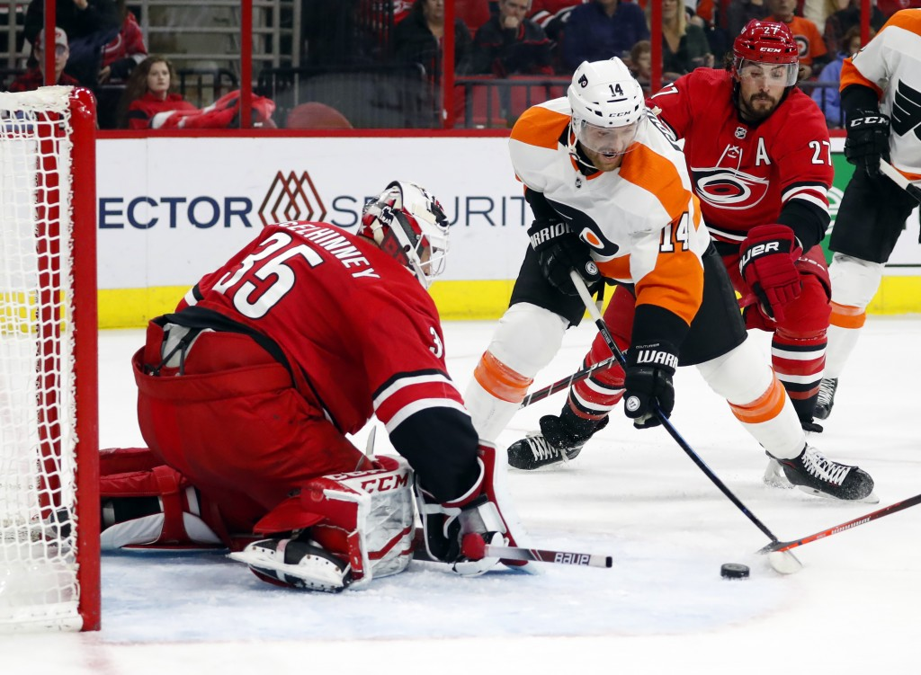 Philadelphia Flyers' Sean Couturier (14) shoots the puck toward Carolina Hurricanes goaltender Curtis McElhinney (35) during the second period of an N