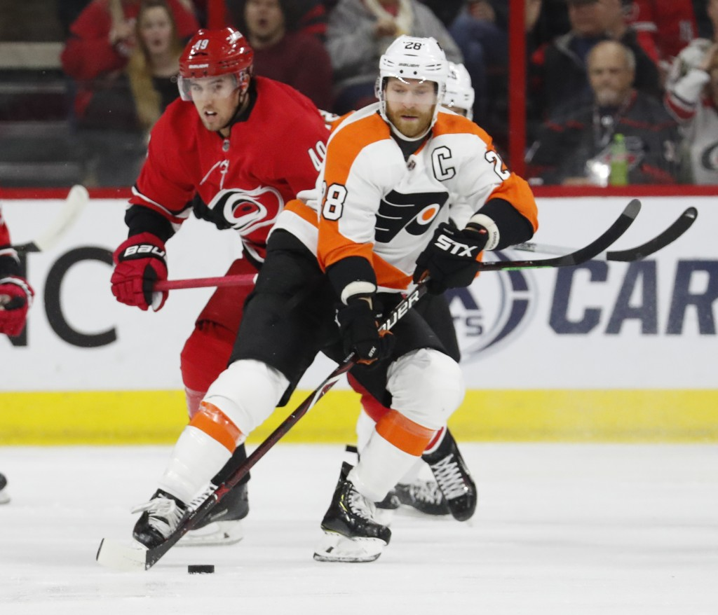 Philadelphia Flyers' Claude Giroux (28) moves the puck after taking it from Carolina Hurricanes' Victor Rask (49) during the first period of an NHL ho