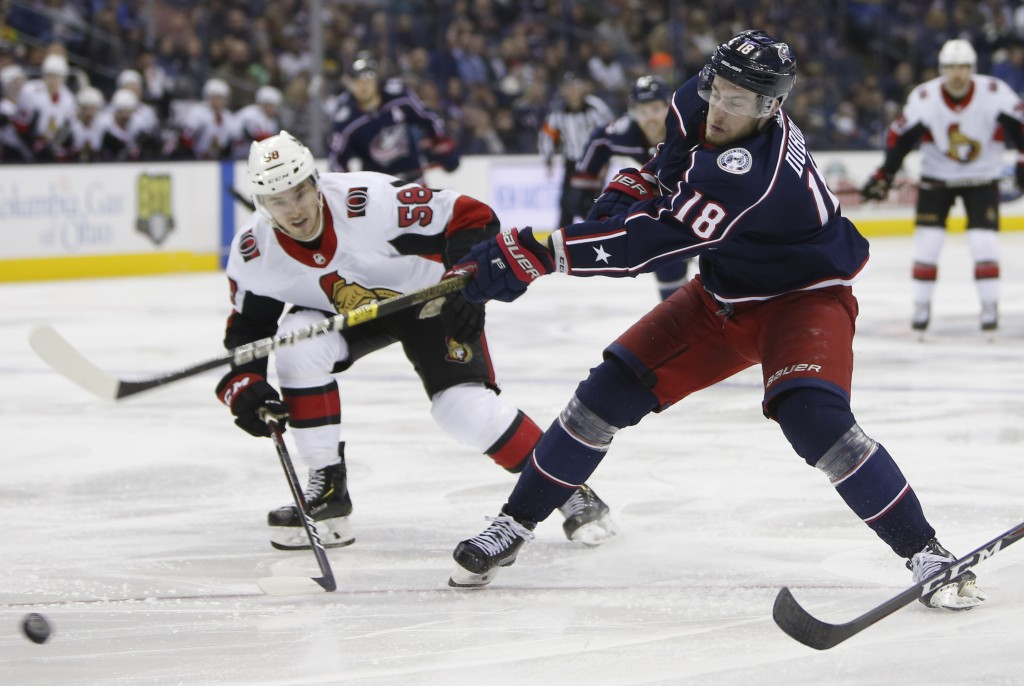 Columbus Blue Jackets' Pierre-Luc Dubois, right, shoots the puck as Ottawa Senators' Maxime Lajoie defends during the second period of an NHL hockey g...