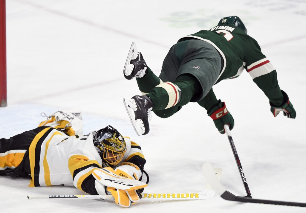 Pittsburgh Penguins goaltender Casey DeSmith (1) covers the puck as Minnesota Wild center Luke Kunin (19) jumps over him during the first period of an...