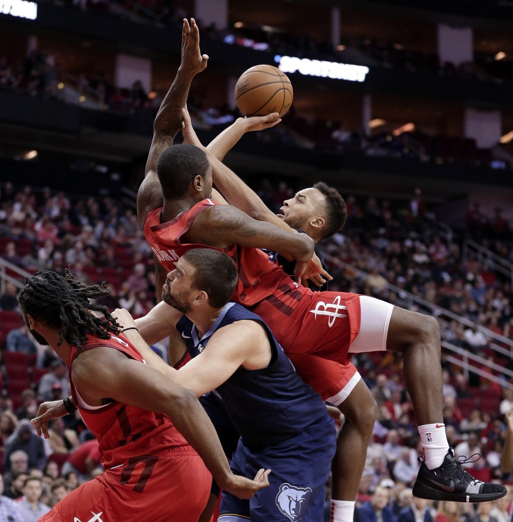 Memphis Grizzlies forward Kyle Anderson, right, shoots as Houston Rockets forward Gary Clark, top, falls onto center Marc Gasol, who pushes off of Hou...