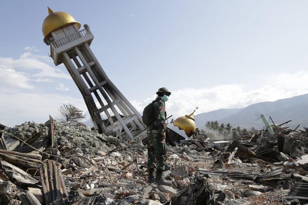 FILE - In this Oct. 6, 2018 file photo, a soldier stands near a toppled mosque as recovery efforts continue at the earthquake-hit Balaroa neighborhood