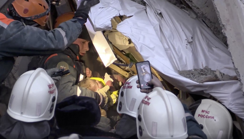 This photo provided by the Russian Emergency Situations Ministry taken from tv footage shows Emergency Situations employees save a 10 month old baby a