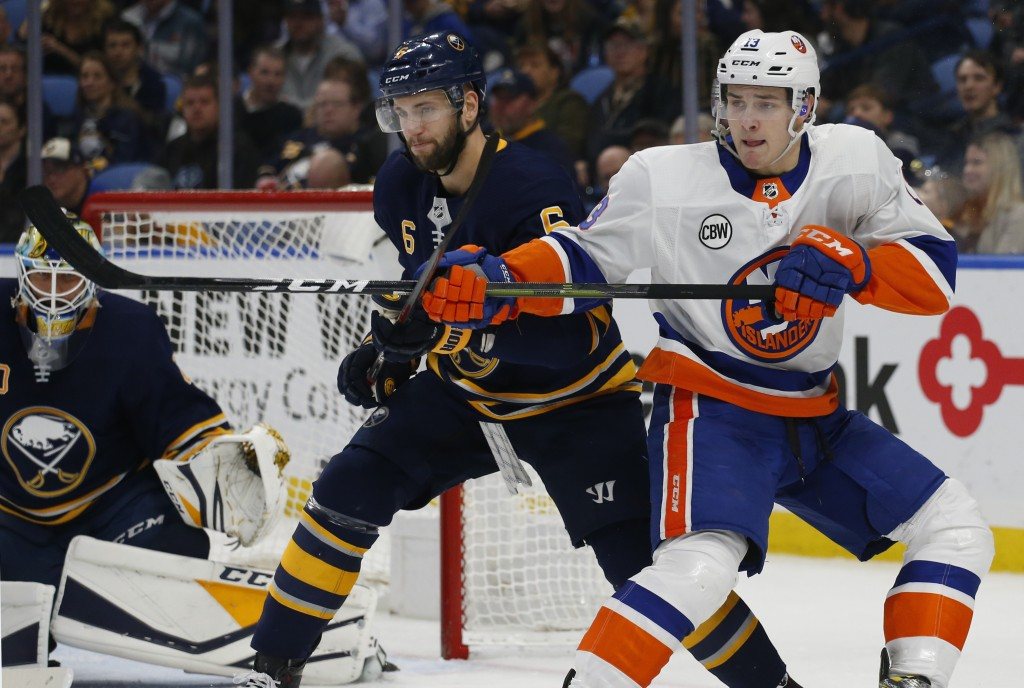 Buffalo Sabres defenseman Marco Scandella (6) and New York Islanders forward Mathew Barzal (13) battle for position during the second period of an NHL...
