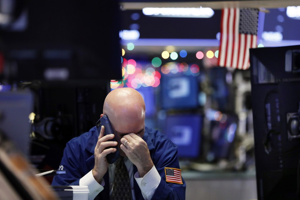 A trader talks on his phone on the floor of the New York Stock Exchange, Wednesday, Jan. 2, 2019. Stock markets started the new year with a tumble, as