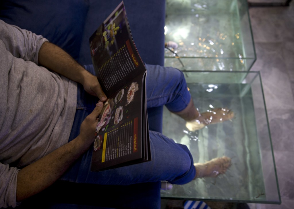 In this Wednesday, Dec. 26, 2018 photo, a man soaks his feet in tank stocked with fish while looking at a menu at a hookah bar and cafe in Gaza City.