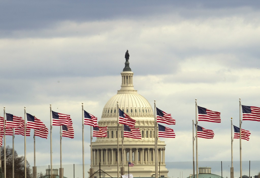 Flags fly in front of the U.S. Capitol in Washington, Tuesday morning, Jan. 1, 2019, as a partial government shutdown stretches into its third week.  ...