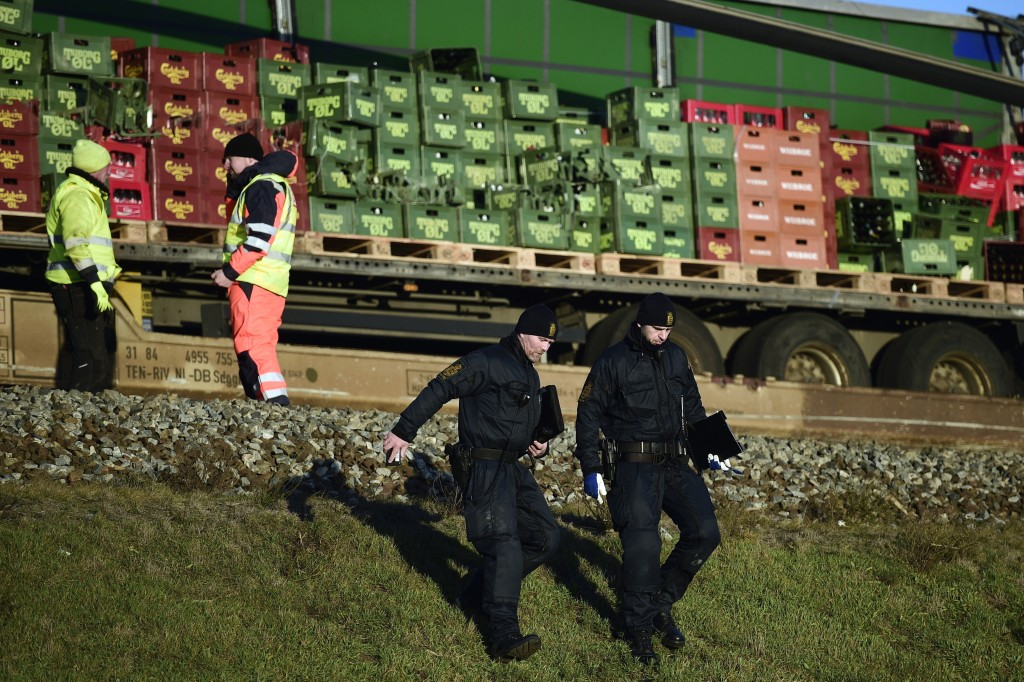 Police walk by a freight train after a train accident on the Great Belt Bridge in Nyborg, Denmark, Wednesday, Jan. 2, 2019.  A Danish passenger train