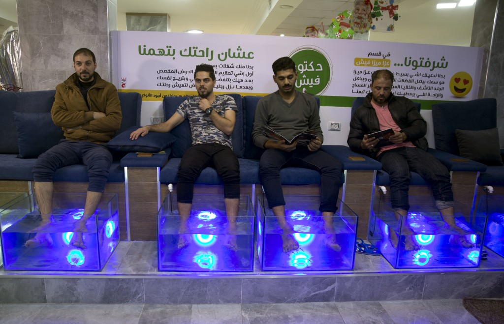 In this Wednesday, Dec. 26, 2018 photo, Palestinians soak their feet in tank stocked with fish at a cafe in Gaza City. The Gaza cafe operator said his