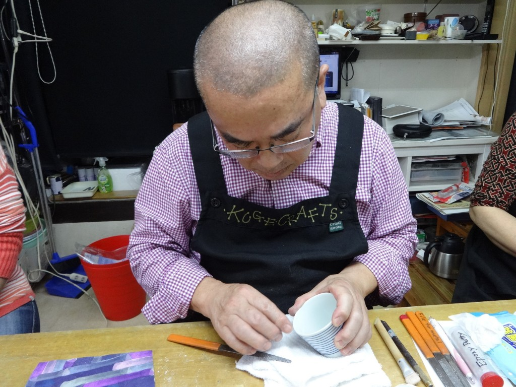 This Nov. 11, 2018 photo taken in Tokyo shows co-instructor Yoshiichiro Kuge checking whether the filler material is filed down enough to proceed to t